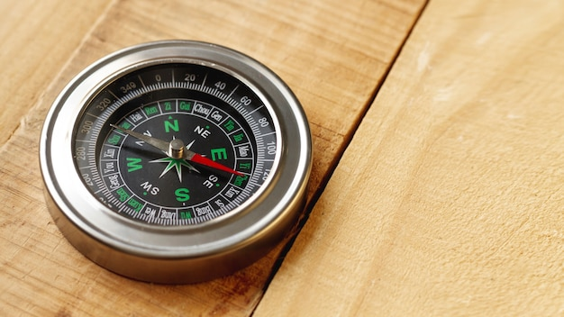 High angle compass on wooden board with copy-space