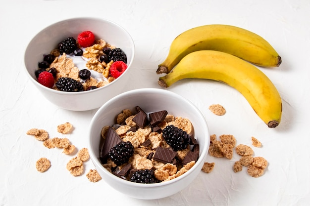 Composizione ad alto angolo di cereali sani ciotola con cioccolato e banane