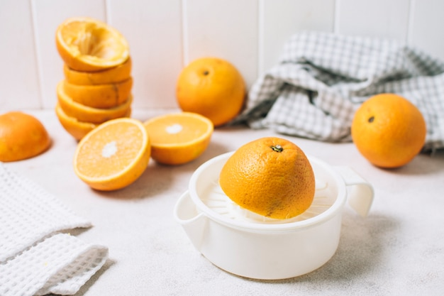 High angle composition with halved oranges and juicer