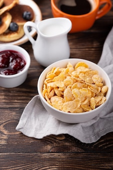 High angle of corn flakes for breakfast in  bowl with milk and jam