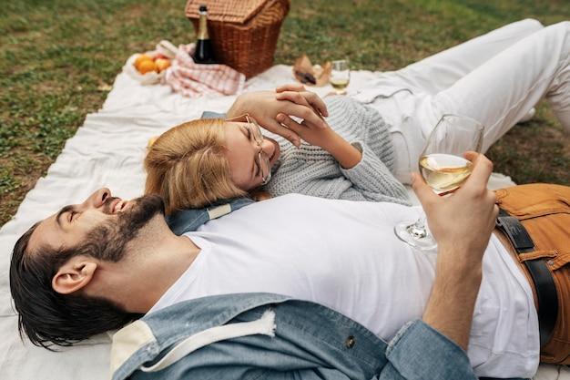 屋外で一緒にピクニックをしているハイアングルカップル
