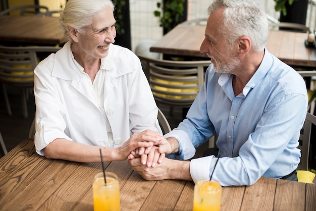 High angle couple holding hands at restaurant