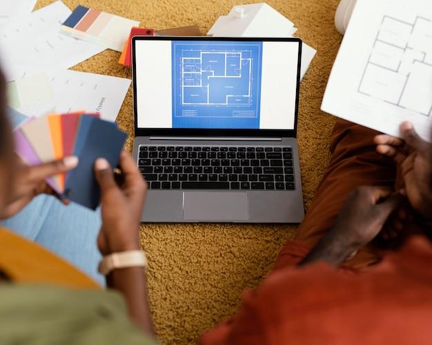Alto angolo di coppia che fa piani per ristrutturare casa utilizzando la tavolozza dei colori e il laptop