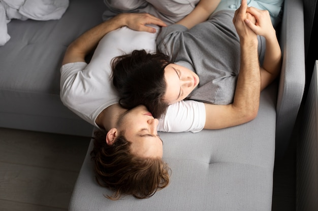 High angle of couple sleeping on sofa