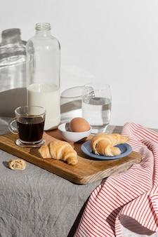 Alto angolo di croissant sul piatto e uova con latte