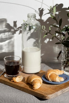High angle of croissants on plate with coffee and milk