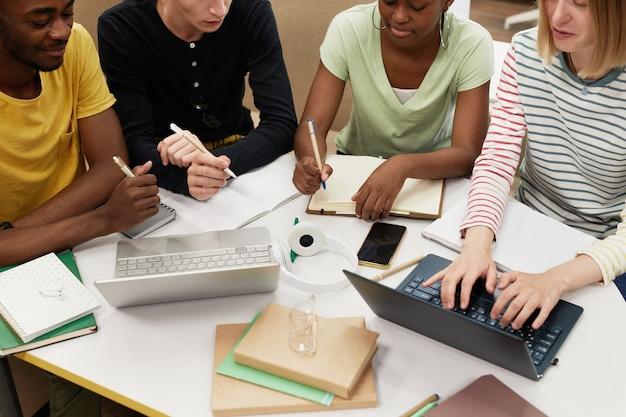 Обрезанный снимок с высоким углом разной группы студентов, работающих вместе за столом в библиотеке.