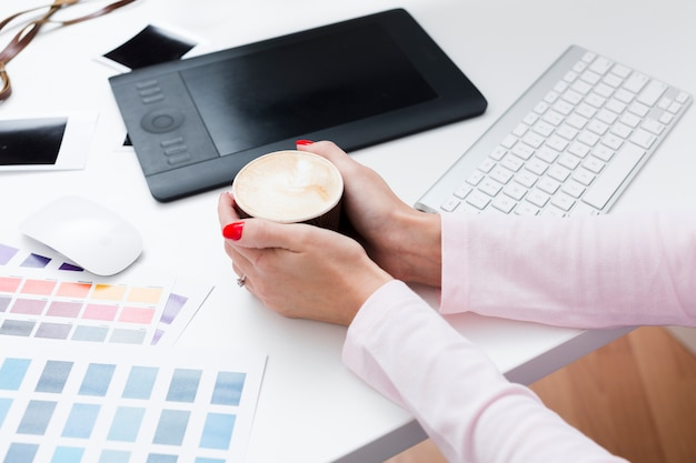 High angle of cup of coffee held by woman on desk