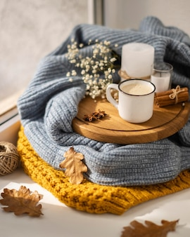 High angle of cup of coffee with sweater and leaves