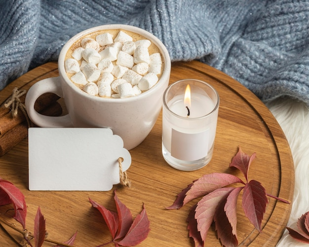 High angle of cup of hot cocoa with marshmallows and candle