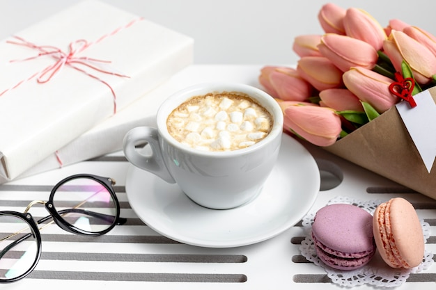 High angle of cup of marshmallows with tulips and present