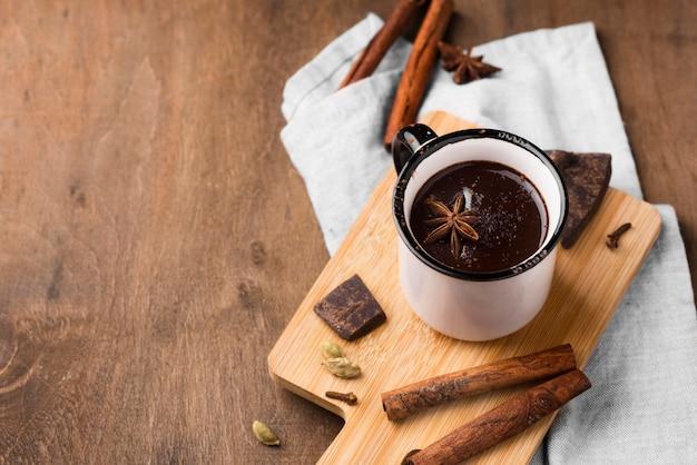 Чашка под высоким углом с горячим шоколадом и корицей