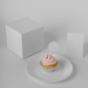 High angle of cupcake with packaging box and plate