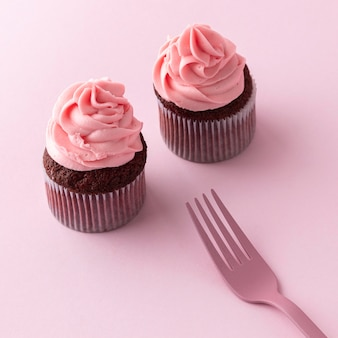 High angle cupcakes with pink icing and fork