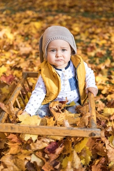High angle cute baby with hat sitting outdoors