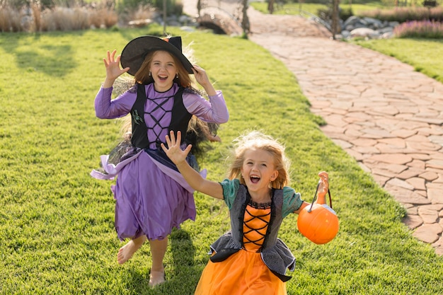 High angle of cute little girls with halloween costumes