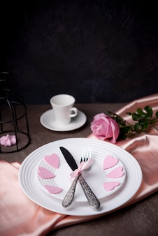 High angle of cutlery on plates with hearts and copy space