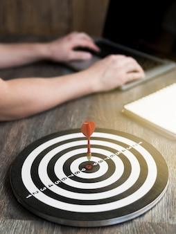 High angle of dart struck in bull's-eye on desk