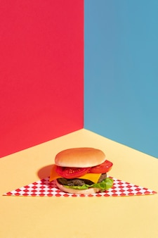High angle decoration with tasty cheeseburger on yellow table