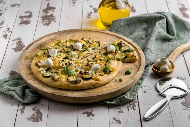 Alto angolo di deliziosa pizza cotta con fiori di camomilla e taglierina