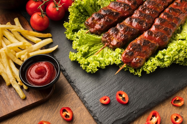 High angle of delicious kebab on slate with tomatoes and fries