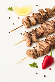 High angle of delicious kebab with chili pepper and lemon