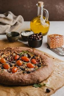 Alto angolo di deliziosa pizza con pomodori e parmigiano