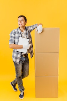 High angle delivery man beside stack of packages