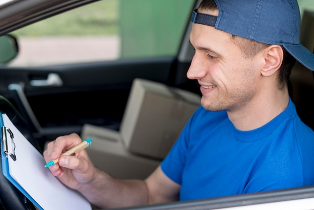 High angle delivery man signing paper