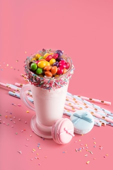 High angle of dessert with colorful candy and straws