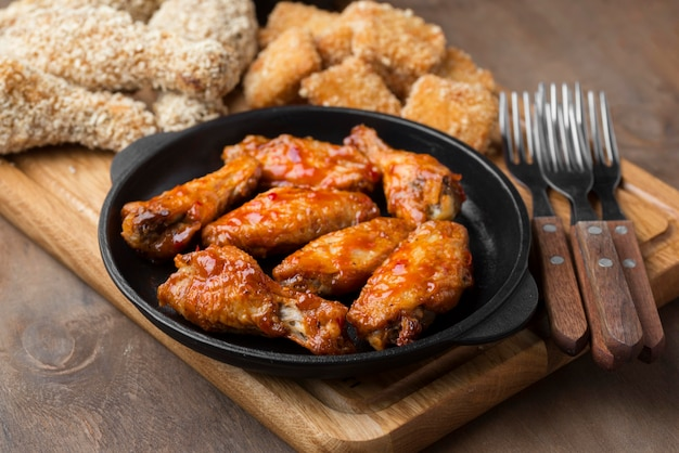 Alto angolo di diversi tipi di pollo fritto con posate