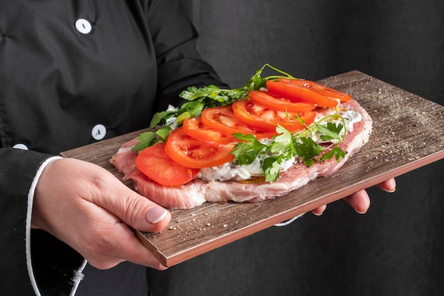 High angle of dish with tomatoes held by female chef
