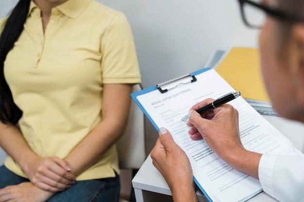 Врач под высоким углом консультирует пациента в ее офисе