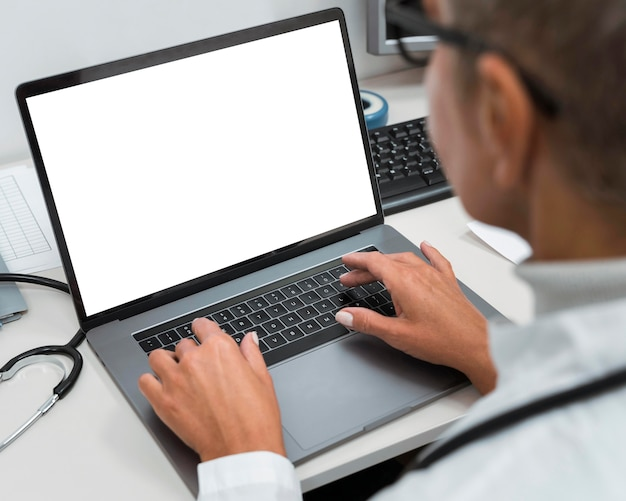 High angle doctor working on a laptop