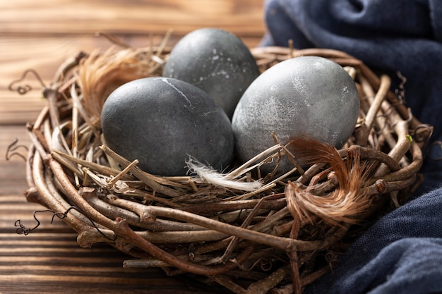 High angle of easter eggs in bird nest with feathers and textile