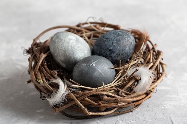 Angolo alto delle uova di pasqua nel nido dell'uccello con le piume
