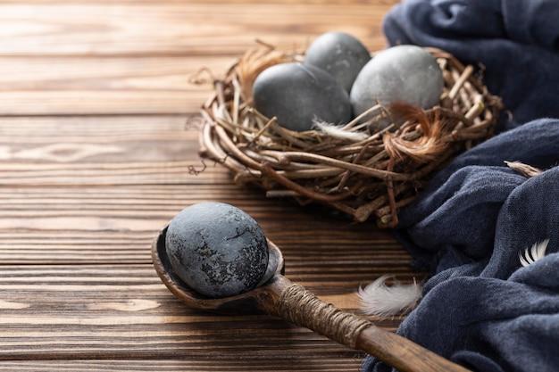 Angolo alto delle uova di pasqua nel nido dell'uccello con il cucchiaio di legno e della tessile
