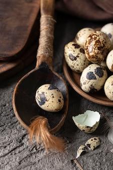 Alto angolo di uova di pasqua con gusci rotti e cucchiaio di legno