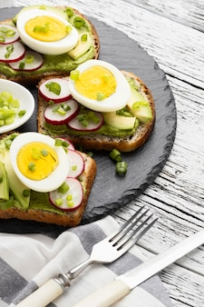High angle of egg and avocado sandwiches on slate with cutlery