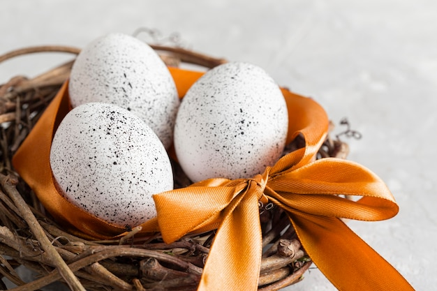 High angle of eggs for easter in bird nest with ribbon and bow