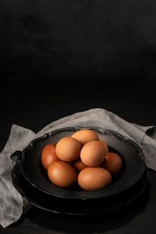 キッチンタオルとコピースペースのボウルに高角度の卵