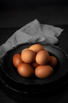 Яйца под высоким углом в миске с кухонным полотенцем