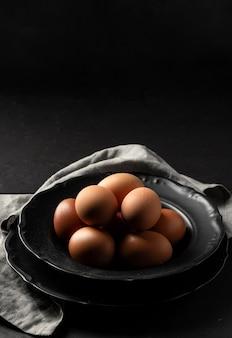 Яйца под высоким углом на тарелке с кухонным полотенцем и копией пространства