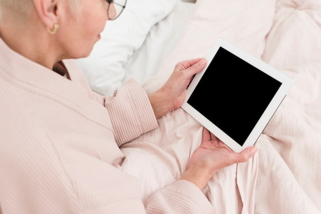 High angle of elderly woman in bed holding tablet