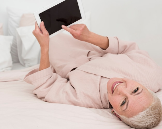 High angle of elderly woman posing and smiling while holding tablet