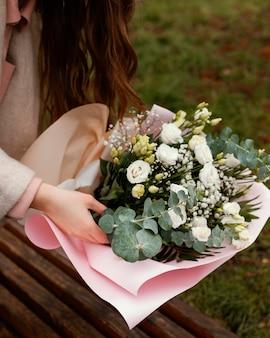 Alto angolo di donna elegante con bouquet di fiori all'aperto
