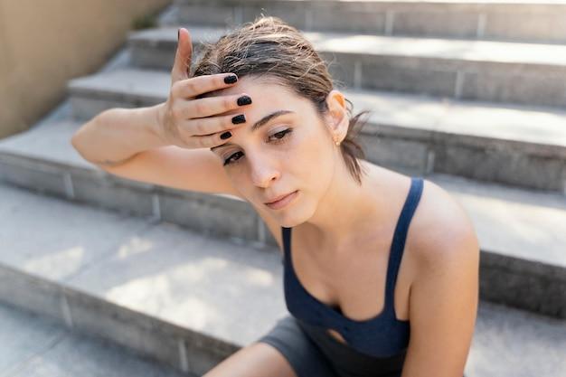Alto angolo di donna esausta che riposa sulle scale dopo l'esercizio