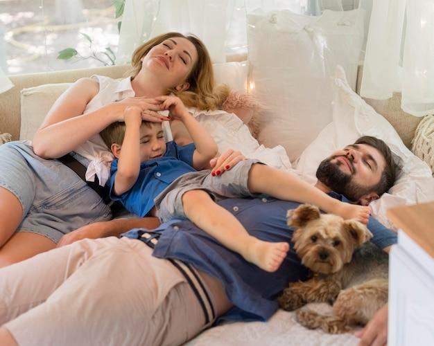 Famiglia ad alto angolo che soggiorna nel letto del caravan con il cane