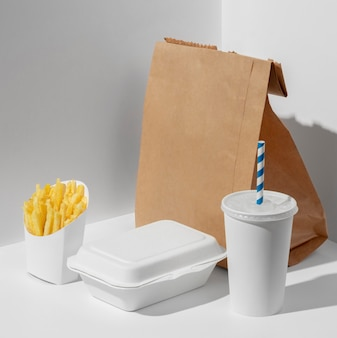 High angle fast food cup with packaging fries and blank paper bag