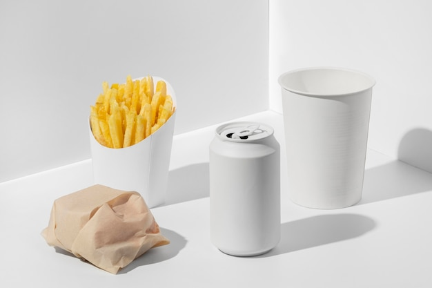 Hamburger confezionato fast food ad alto angolo con soda vuota e tazza con patatine fritte